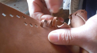 A close up of a hand working on a leather stich