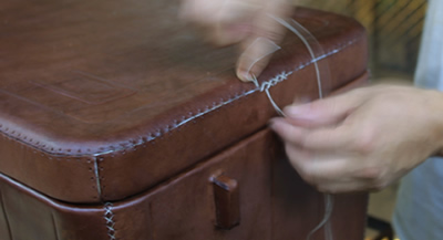 Image of a close up from two hands stiching leather, covering a cooler from Sol&Luna