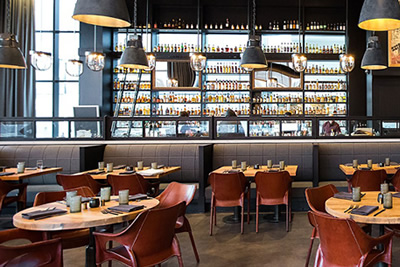 Restaurant of Hotel Denver with Sol&Luna leather Capiata Chairs and the bar at the back