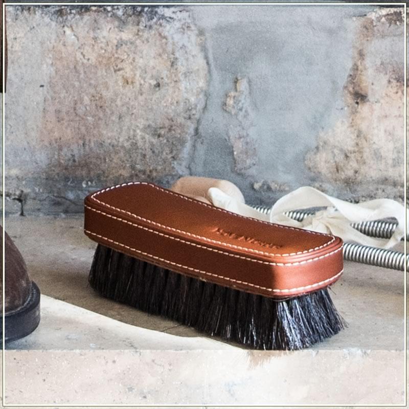 Imagen de un cepillo de zapatos, forrado en cuero marrón, apoyado en el suelo delante de una chimenea